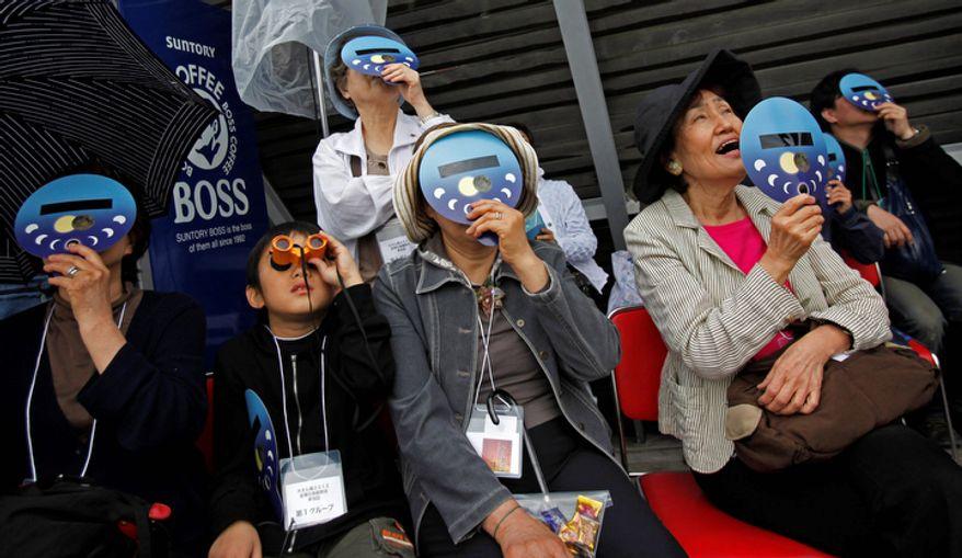 People view an annular solar eclipse at a waterfront park in Yokohama, near Tokyo.  (AP Photo/Shuji Kajiyama)