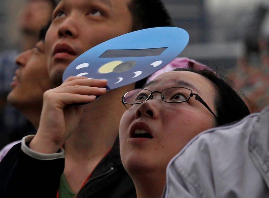 A woman reacts as she views an annular solar eclipse at a waterfront park in Yokohama, near Tokyo.   (AP Photo/Shuji Kajiyama)