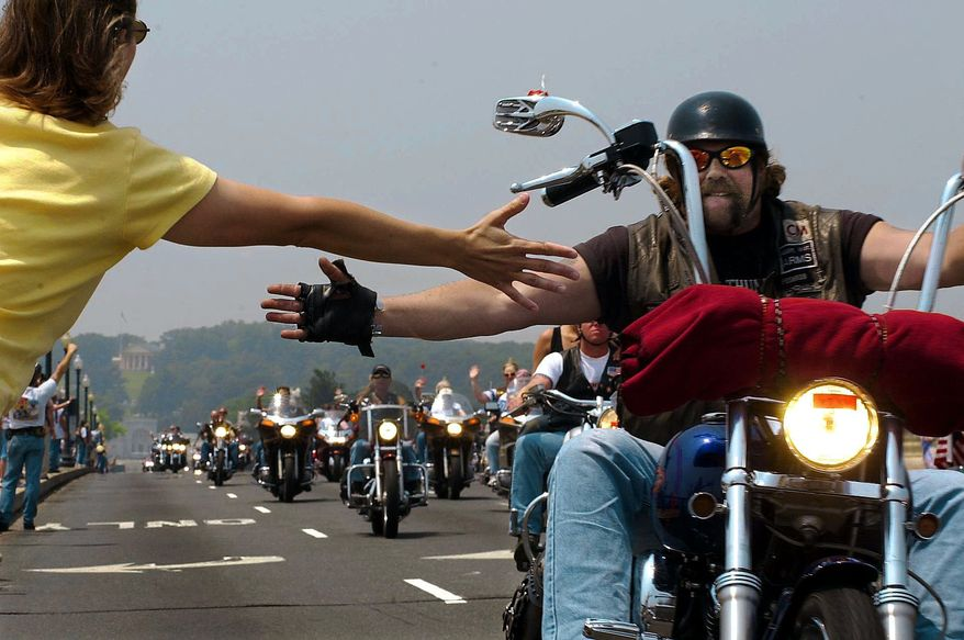 During Rolling Thunder, Rose Harrelson, left, greets bikers as they come across the Memorial Bridge. Sunday, May 26, 2002 ( Damiel Rosenbaum / The Washington Times )