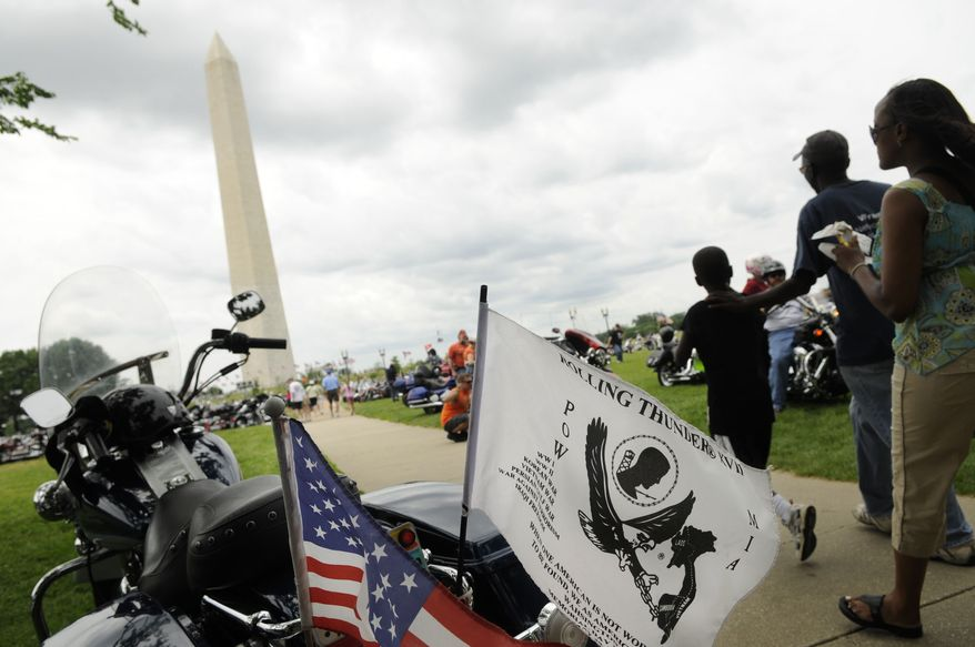 Isaac Katongole, 8, walks with his father Meddie Katongole, and Meddie's fiancee Mercy Mbogori, as they stroll past parked motorcycles on The National Mall, during the Rolling Thunder XXII Ride for Freedom along Constitution Avenue in Washington, D.C., Sunday, May 24, 2009.  (Rod Lamkey Jr. / The Washington Times)
