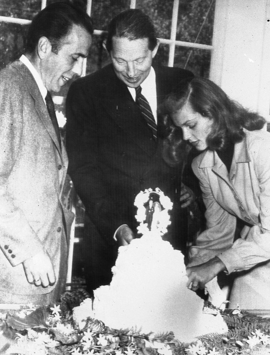 Novelist Louis Bromfield (center) watches Lauren Bacall cut the cake after her marriage to Humphrey Bogart (left) at Bromfield's Ohio farm. Son Stephen Bogart is helping raise funds to renovate the home where his parents were married. (Associated Press)