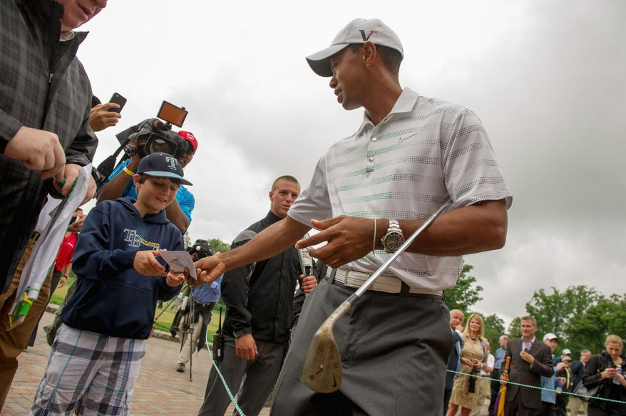 Tiger Woods signs an autograph for Joey Ramsbottom, 10, of Goochland, Va., after holding a chipping contest as a lead up to the AT&T National golf tournament at Congressional Country Club, Bethesda, Md., Monday, May 21, 2012. (Andrew Harnik/The Washington Times)