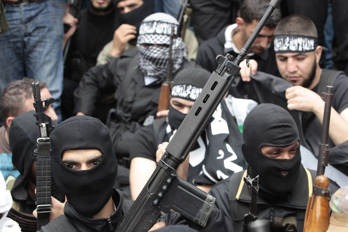 Masked Sunni gunmen hold their weapons May 21, 2012, as they attend the funeral procession of anti-Syrian regime Sunni cleric Sheik Ahmed Abdul-Wahid, who was shot at a Lebanese army checkpoint, at his hometown village of Beireh, Lebanon. (Associated Press)