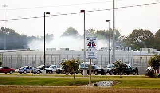 Smoke rises above the Adams County Correctional Center in Natchez, Miss., on Sunday, May 20, 2012, during an inmate disturbance. (AP Photos/Natchez Democrat, Lauren Wood)