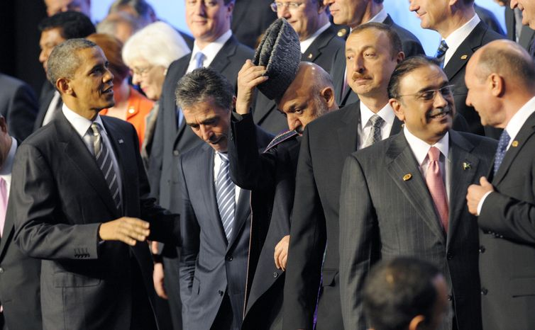 From left, President Barack Obama, NATO Secretary General Anders Fogh Rasmussen, Afghan President Hamid Karzai, Azerbaijani President Ilham Aliyev and Pakistani President Asif Ali Zardari talk during a family picture of NATO leaders at the NATO Summit in Chicago, Monday, May 21, 2012. (AP Photo/Philippe Wojazer, Pool)