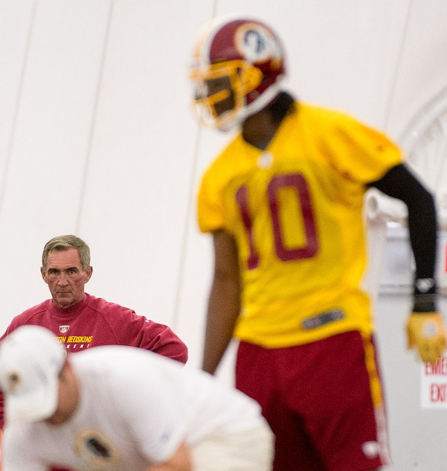 Washington Redskins Head Coach Mike Shanahan, left, watches as  Washington Redskins quarterback Robert Griffin III (10), right, as he takes snaps on the first day of organized team activity at Redskins Park, Ashburn, Va., Monday, May 21, 2012. (Andrew Harnik/The Washington Times)