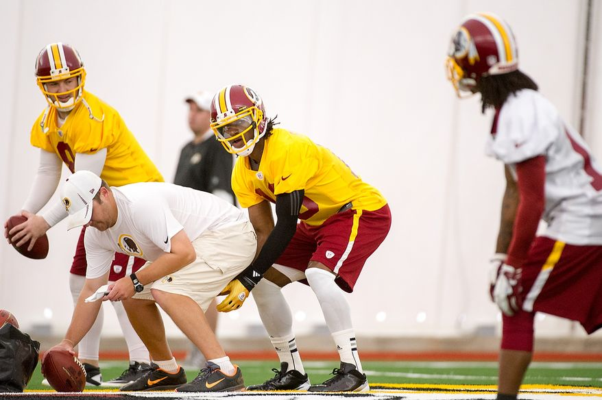 Washington Redskins quarterbacks Rex Grossman (8), left, and Robert Griffin III (10), second from right, take snaps together on the first day of organized team activity at Redskins Park, Ashburn, Va., Monday, May 21, 2012. (Andrew Harnik/The Washington Times)