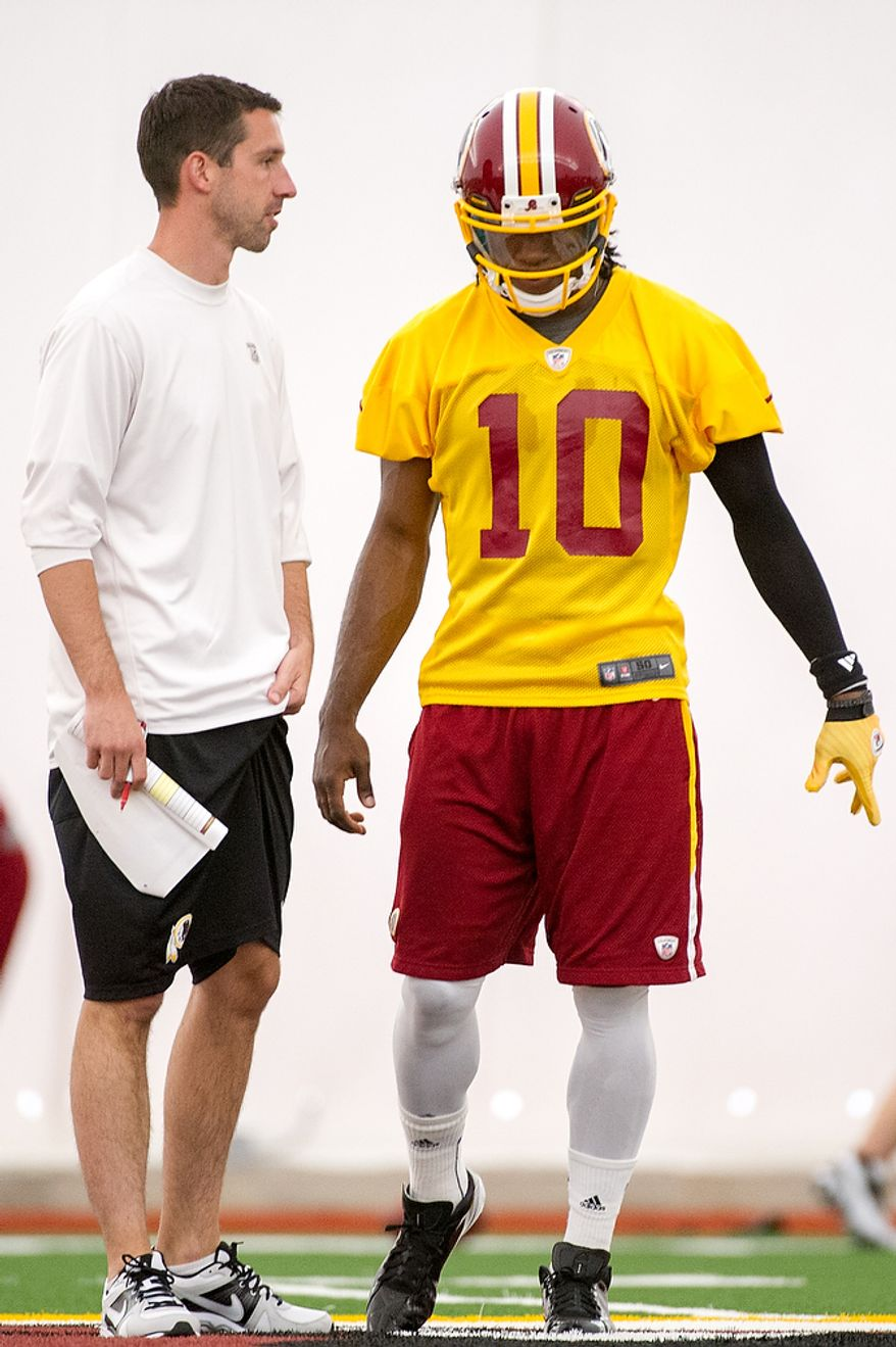 Washington Redskins offensive coordinator Kyle Shanahan, left, work quarterback Robert Griffin III (10), on the first day of organized team activity at Redskins Park, Ashburn, Va., Monday, May 21, 2012. (Andrew Harnik/The Washington Times)
