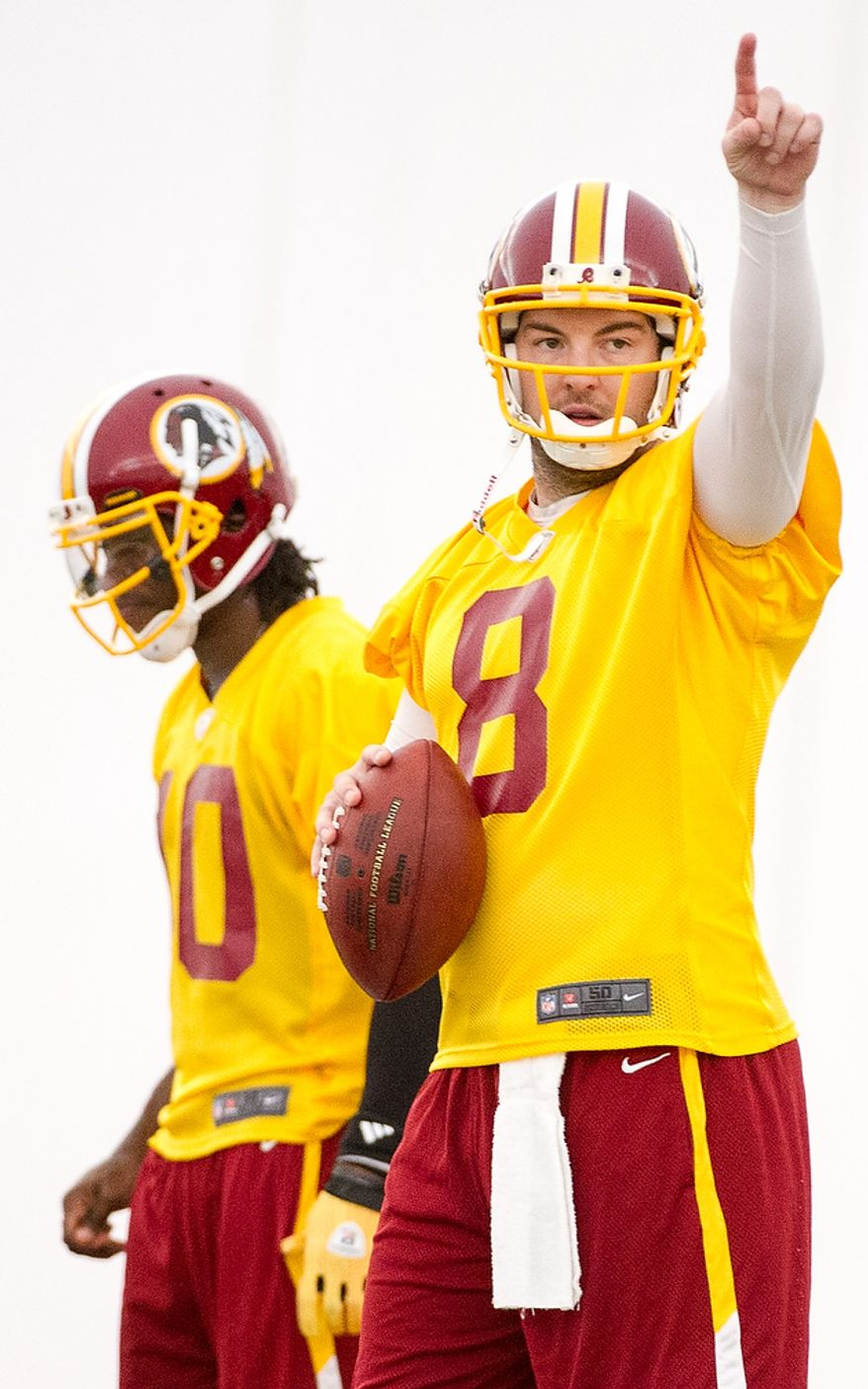 Washington Redskins quarterbacks Rex Grossman (8), right, and Robert Griffin III (10), left, take snaps together on the first day of organized team activity at Redskins Park, Ashburn, Va., Monday, May 21, 2012. (Andrew Harnik/The Washington Times)