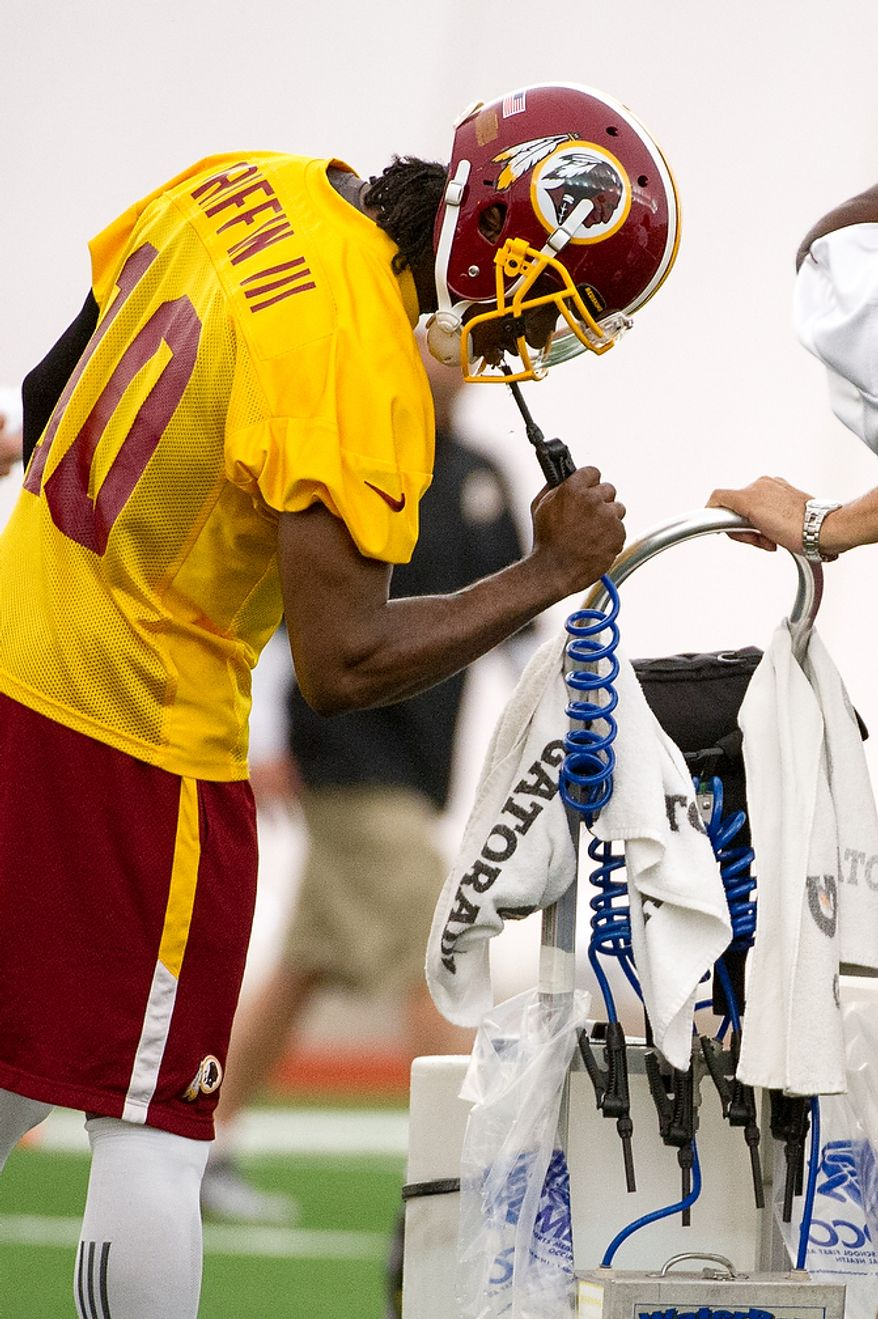 Washington Redskins quarterback Robert Griffin III gets water during the first day of organized team activity at Redskins Park, Ashburn, Va., Monday, May 21, 2012. (Andrew Harnik/The Washington Times)