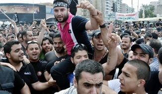 Shadi Mawlawi (center), a Lebanese critic of the Syrian regime who was accused of belonging to a terrorist group, is carried on his friends' shoulders as they celebrate his release from jail in the northern port city of Tripoli, Lebanon, on Tuesday. Earlier this month, his arrest set off several days of clashes. (Associated Press)