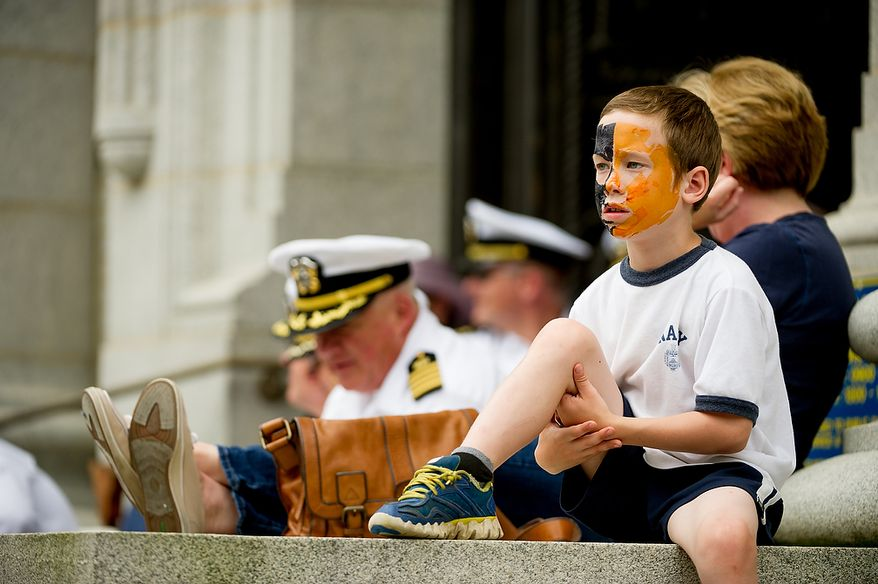 """Malachi Leary, 8, of Wooster, Mass., right, sporting Navy colors, watches as his sister, a first year Naval Academy plebe, participates along with her classmates in the traditional Herndon Monument climb, Annapolis, Md., Tuesday, May 22, 2012. The tradition, dating back to 1940, is the culmination of the first year in the Naval Academy where the plebe class has to help each other climb the obelisk covered in lard, remove the """"dixie cup"""" hat at the top and replace it with an upperclassman's hat. (Andrew Harnik/The Washington Times)"""