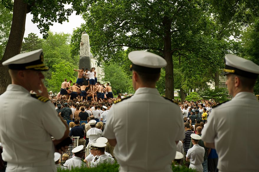 """First year Naval Academy plebes participate in the traditional Herndon Monument climb which marks the culmination of their first year, Annapolis, Md., Tuesday, May 22, 2012. The tradition, dating back to 1940, involves the entire plebe class working with each other to climb the obelisk covered in lard, remove the """"dixie cup"""" hat at the top and replace it with an upperclassman's hat. (Andrew Harnik/The Washington Times)"""