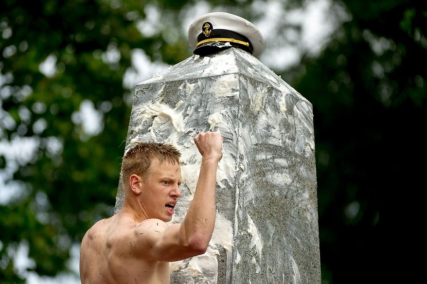 """Midshipman 4th Class Andrew Craig, 19, of Tulsa, Okla., replaces a first year's Naval Academy """"dixie cup"""" hat with an upperclassman's hat as the plebes finish the traditional Herndon Monument climb in two hours and ten minutes, Annapolis, Md., Tuesday, May 22, 2012. The tradition, dating back to 1940, is the culmination of the first year in the Naval Academy where the plebe class has to help each other climb the obelisk covered in lard. (Andrew Harnik/The Washington Times)"""