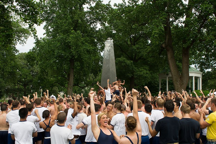 """First year Naval Academy plebes celebrate as they finish the traditional Herndon Monument climb in two hours and ten minutes, Annapolis, Md., Tuesday, May 22, 2012. The tradition, dating back to 1940, is the culmination of the first year in the Naval Academy where the plebe class has to help each other climb the obelisk covered in lard, remove the """"dixie cup"""" hat at the top and replace it with an upperclassman's hat. (Andrew Harnik/The Washington Times)"""