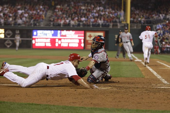 Washington Nationals catcher Jesus Flores, right, tags out Philadelphia Phillies' Placido Polanco at home after Polanco tried to score on fielder's choice by Philadelphia Phillies' Carlos Ruiz in the sixth inning of a baseball game, Monday, May 21, 2012, in Philadelphia. (AP Photo/Matt Slocum)