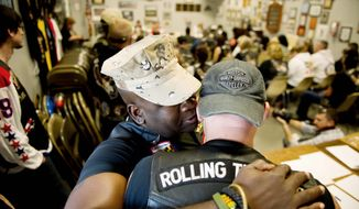 Marine Cpl. Joe Coaxum whispers something to Air Force Chief Master Sgt. Daryl Web as Rolling Thunder's Maryland chapter holds a general membership meeting at the Harley-Davidson motorcycle shop in Fort Washington on May 12 to plan its Memorial Day weekend events. (Andrew Harnik/The Washington Times)