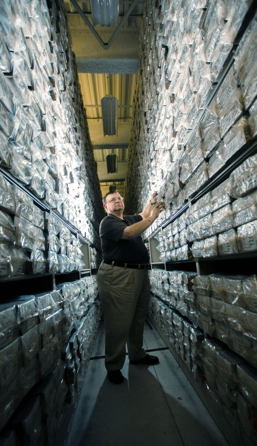 James Canik, deputy director of the Armed Forces DNA Identification Laboratory, searches among the vacuum-sealed DNA samples stored at the Armed Forces Repository of Specimen Samples at Dover Air Force Base. (Andrew S. Geraci/The Washington Times)