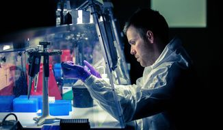 Tim Herbert, an analyst at the Armed Forces DNA Identification Laboratory at Dover Air Force Base, tests a DNA specimen sample. The lab houses more than 6.7 million boxes of DNA samples. (Andrew S. Geraci/The Washington Times)