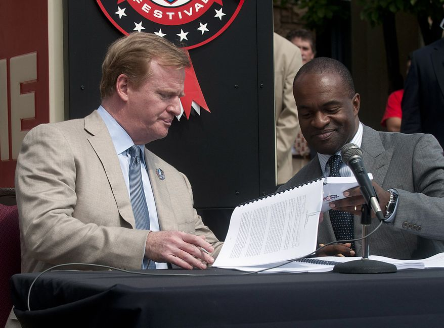 **FILE** NFL Commissioner Roger Goodell (left) and NFLPA Executive Director Demaurice Smith exchange papers Aug. 5, 2011, as they sign their collective bargaining agreement at the Pro Football Hall of Fame in Canton, Ohio. (Associated Press)