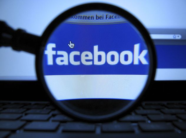 ** FILE ** In this Oct. 10, 2011, file photo, a magnifying glass is posed over a monitor displaying a Facebook page in Munich. (AP Photo/dapd, Joerg Koch)