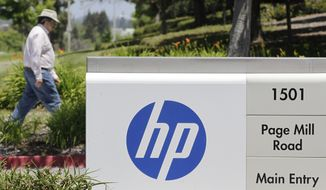 A Hewlett-Packard worker walk in the main entrance of HP Headquarters in Palo Alto, Calif., Thursday, May 17, 2012. (AP Photo/Paul Sakuma)