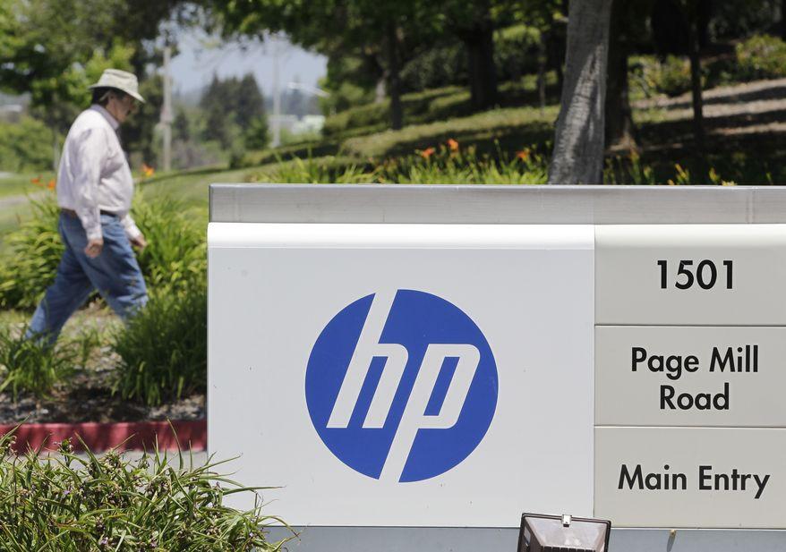 A Hewlett-Packard worker walk in the main entrance of HP Headquarters in Palo Alto, Calif., Thursday, May 17, 2012. (AP Photo/Paul Sakuma)