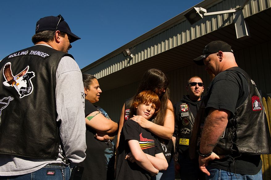 Jim Shekleton of Waldorf, Md., right, watches as his wife Britney, center hugs their son Jason, 10, right, before the Rolling Thunder's Maryland chapter holds a general membership meeting to plan for their Memorial Day events at Harley Davidson's Ft. Washington store, Ft. Washington, Md., Saturday, May 12, 2012. (Andrew Harnik/The Washington Times)