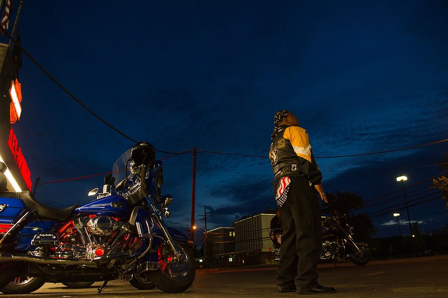 """Air Force Chief Master Sgt. Cornell """"Smokey"""" Langford of Clinton, Md., stares out into the predawn sky as he and other members of Rolling Thunder's Maryland chapter meet in the early morning hours at Harley Davidson's Ft. Washington store before heading to the Vietnam Memorial to help wash the memorial, Ft. Washington, Md., Sunday, May 13, 2012. (Andrew Harnik/The Washington Times)"""