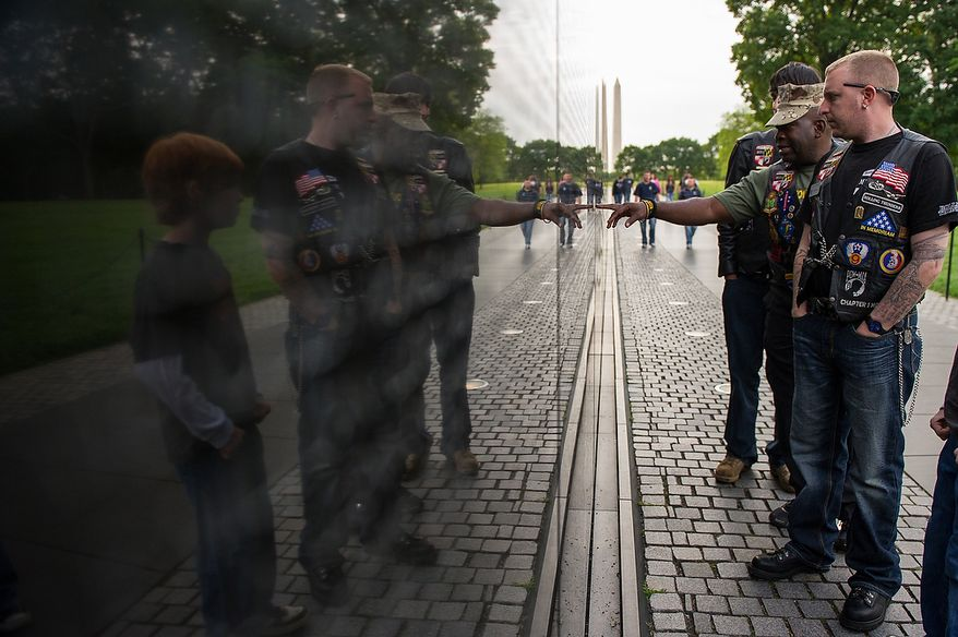 Marine Cpl. Joe Coaxum, second from right, and Army Spc. Cory Lutzow, right, Serving in Afghanistan, looks through some of the names on the wall as Jason Shekleton, 10, in reflection at right, looks on as the Rolling Thunder's Maryland chapter meets in the early morning at the Vietnam Memorial to help wash the memorial, Washington, D.C., Sunday, May 13, 2012. (Andrew Harnik/The Washington Times)