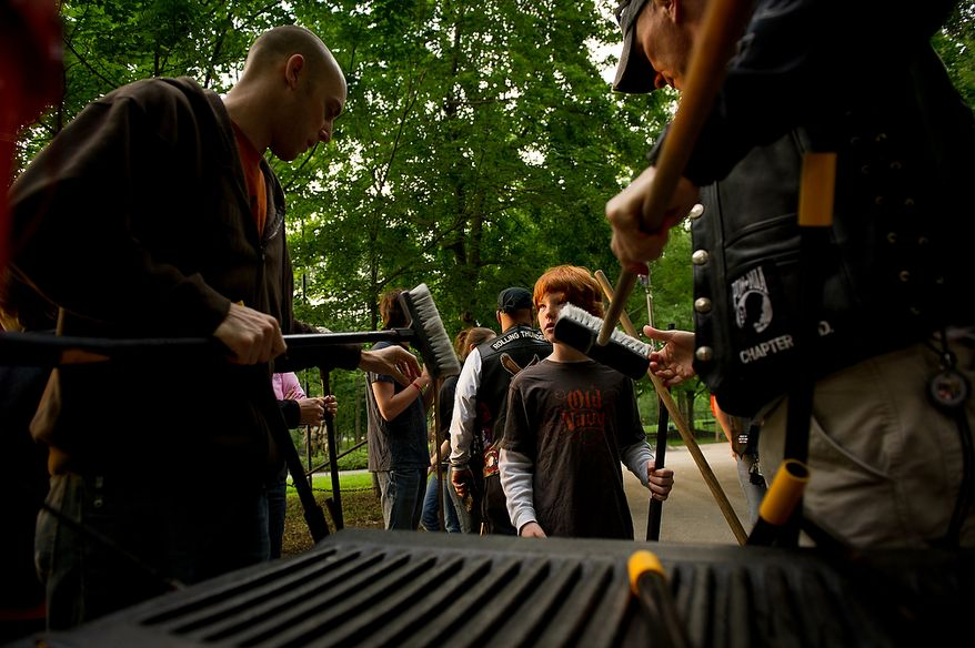 Jason Shekleton, 10, center, helps unload scrub brushes as the Rolling Thunder's Maryland chapter meets in the early morning on the National Mall to help wash the Vietnam Memorial, Washington, D.C., Sunday, May 13, 2012. (Andrew Harnik/The Washington Times)