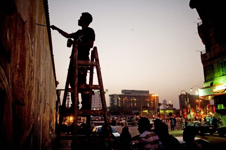A political activist paints a mural on a wall Thursday in Cairo's Tahrir Square. During the uprising that resulted in the ouster of President Hosni Mubarak in 2011, Tahrir Square was the central gathering point for protesters. Since the revolution, many streets leading to the square display murals dedicated to the uprising and those who died in it. (Associated Press)
