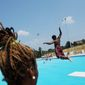 **FILE** Lifeguard Breanna Adams watches as children jump from the diving board at the Anacostia Pool and Recreation Center in Washington, D.C., on July 21, 2011. (Rod Lamkey Jr./The Washington Times)