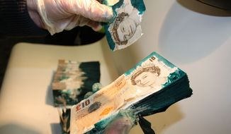 A new security system employed by the G4S security company in the United Kingdom slathers currency with glue and dye when the company's cash boxes are opened improperly. (AP Photo/Courtesy of G4S)