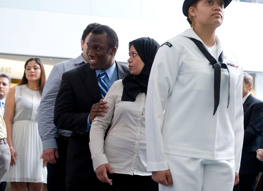 James Mundia, originally of Kenya, grabs Asma Iqbal, originially from Pakistan, as the two wait in line to receive their certificates of citizenship Thursday, May 24, 2012 at a naturalization ceremony at the Smithsonian Institute's National Museum of American History in Washington, D.C. Twelve candidates from 12 different countries became citizens. (Barbara L. Salisbury/The Washington Times)