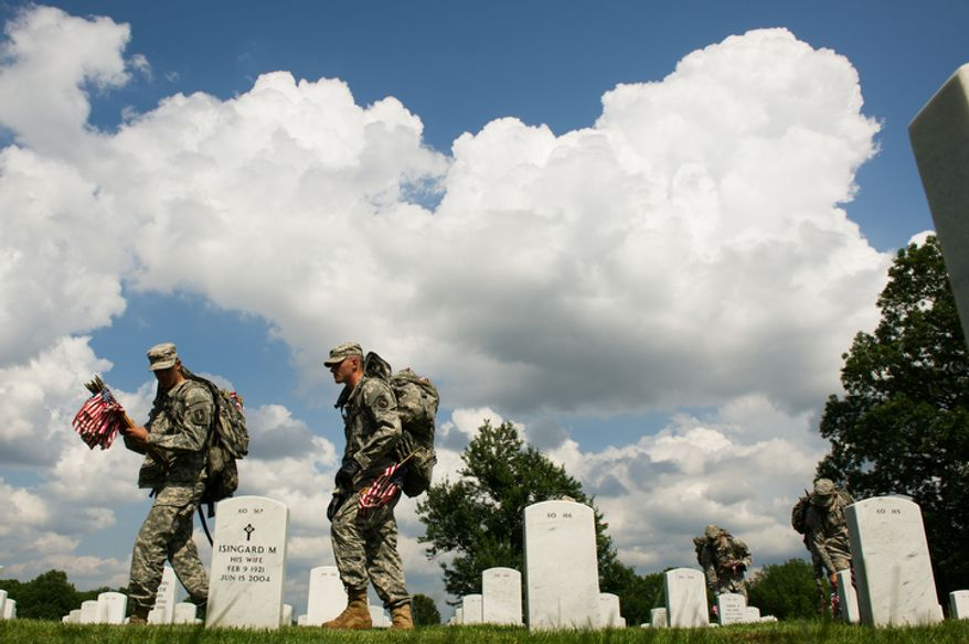 "Pvt. Jose Vazquez, left, and Pvt. Aaron Johnson, second from left, along with other Honor Guard soldiers place flags before each grave in preparation for Memorial Day, during the annual ""Flags-In"" ceremony at Arlington National Cemetery.  (Andrew Harnik/The Washington Times)"