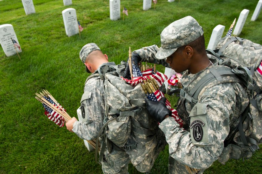 Spc. John Finney, left, and Spc. Kevin Wilson, right, and other Honor Guard soldiers place small America flags at each grave to honor the nation's fallen service members. (Andrew Harnik/The Washington Times)