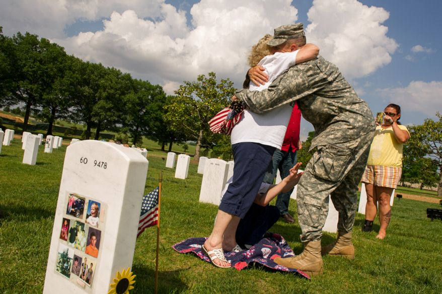 Maj. Gen. Michael S. Linnington, second from right, hugs Audrey Campbell, left, of Chiefland, Fla., visiting the grave of her son, Sgt. Karl Campbell, killed in Afghanistan in 2010, as Linnington and other soldiers place small America flags at each grave at Arlington National Cemetery to honor the nation's fallen service members in Arlington, Va., Thursday, May 24, 2012. Also pictured is Karl Campbell's sister Tina Thomas, right, of Starke, Fla. (Andrew Harnik/The Washington Times)