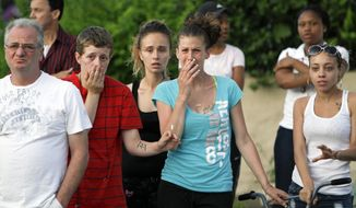 Neighbors in Northeast Philadelphia react as police remove the bodies of toddler twins on Thursday May 24, 2012, after they were found dead in their home. Police say the 18-month-old boy and girl appear to have died of suffocation and the mother is in custody. Police say their 41-year-old mother attempted to take her own life by slitting her wrists and they believe she gave some kind of prescription pills to her 4-year-old daughter. The 4-year-old girl is hospitalized. Information on her condition wasn't available. (AP Photo/Joseph Kaczmarek)