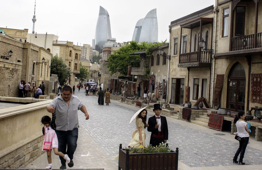 Pedestrians walk in downtown Baku, Azerbaijan, on May 22, 2012. The capital of this former Soviet republic has shed its dour, industrial image and evolved into a vibrant metropolis combining the old world charms of Istanbul with the architectural ostentations of Dubai. (Associated Press)