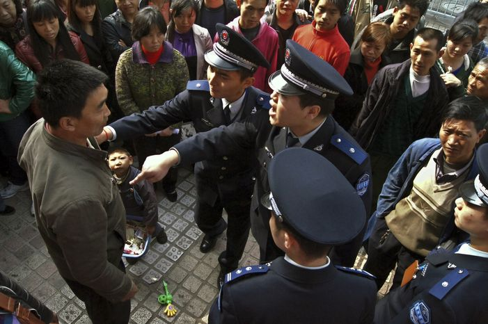 **FILE** Officers of the urban management bureau, known as chengguan in Chinese, demand Nov. 20, 2011, a beggar and his child leave a street in Guiyang, in southwestern China's Guizhou province. (Associated Press)