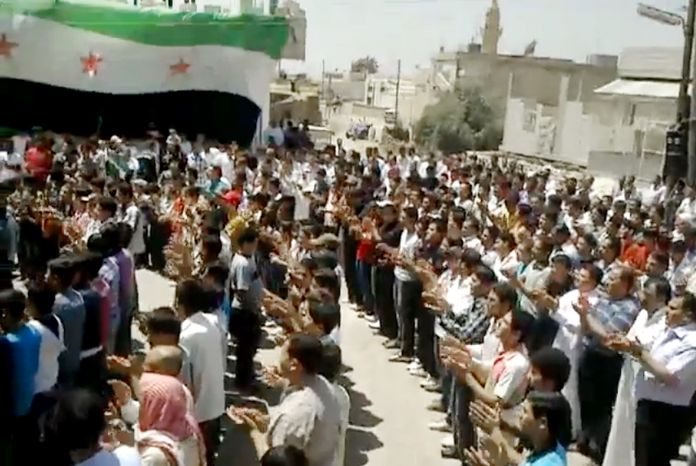 This image made from amateur video released by the Shaam News Network and accessed May 23, 2012, purports to show Syrians chanting slogans during a demonstration in Idlib, Syria. (Associated Press/Shaam News Network via AP video)