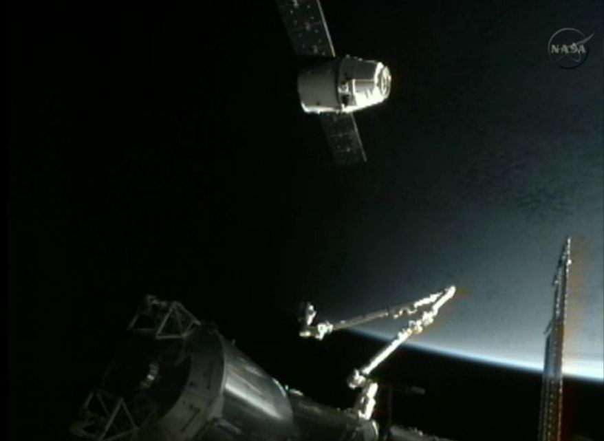 This image provided by NASA-TV shows the SpaceX Dragon commercial cargo craft (top) as it approaches the International Space Station on May 25, 2012. Dragon is scheduled to spend about a week docked with the station before returning to Earth on May 31 for retrieval. (Associated Press/NASA)