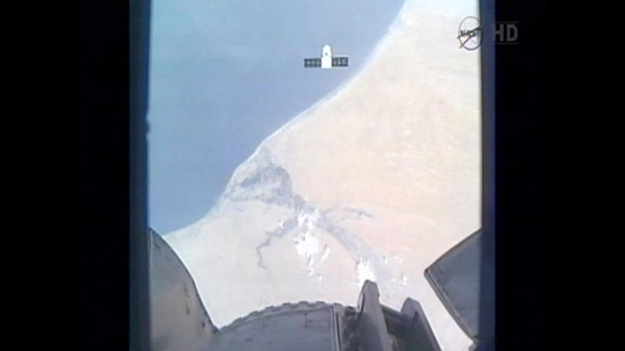 This image provided by NASA-TV shows the SpaceX Dragon commercial cargo craft as it flies over the coast of West Africa taken from Canadarm2's video camera as Dragon approaches the International Space Station early May 25, 2012. In foreground is a portion of Canadarm2. (Associated Press/NASA)