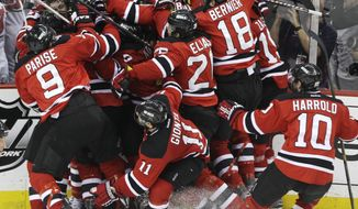 The New Jersey Devils celebrate after beating the New York Rangers 3-2 in overtime to advance to the Stanley Cup finals. (AP Photo/Frank Franklin II)
