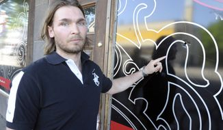 Survivor Miikka Jaske points to a bullet hole whilst standing at the same point where he was standing during the shooting, outside the restaurant Medicine Man in Hyvinkaa, Finland, Saturday May 26, 2012. (AP Photo/Lehtikuva, Jussi Nukari)