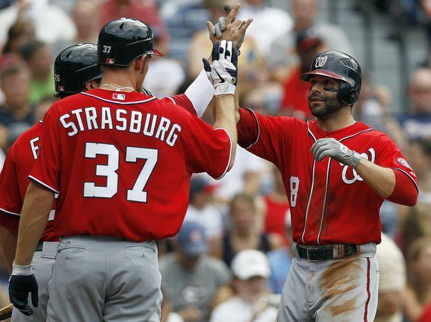 Washington Nationals' Danny Espinosa celebrates with Stephen Strasburg after hitting a three-run home run in the second inning against the Atlanta Braves on Saturday, May 26, 2012, in Atlanta. (AP Photo/John Bazemore)