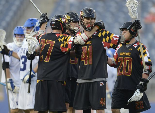 Maryland's Kevin Cooper (41) celebrates a fourth-quarter goal with teammates, from left, Kevin Forster, Owen Blye and Billy Gribbin (20) during an lacrosse semifinal match against Duke at Gillette Stadium in Foxborough, Mass., on Saturday, May 26, 2012. (AP Photo/Gretchen Ertl)