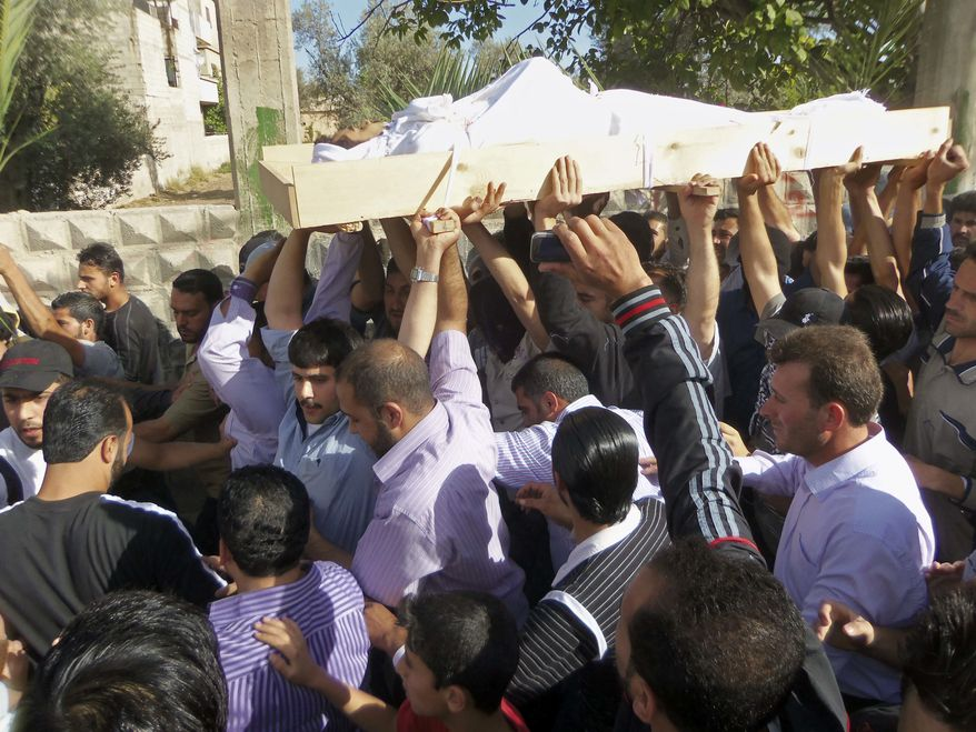 Anti-Syrian regime mourners chant slogans as they carry the body of soldier Khaled Shurbajy, who was shot by Syrian security forces in Dir el Zour last week after disobeying orders to fire on anti-Assad protesters, during his funeral procession, in the Kfar Suseh area of Damascus, Syria, on Saturday , May 26, 2012. (AP Photo)