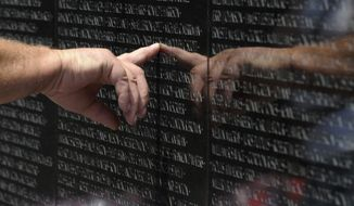 A visitor to the Vietnam Veterans Memorial touches the name of a fallen soldier etched on the wall of the memorial in Washington, Friday, May 25, 2012. (AP Photo/Susan Walsh)